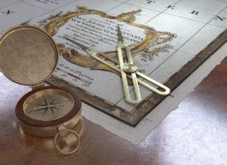Compass, old map and dividers on elm table